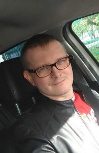 На фотографии мужчина, канцелярщик, сидящий за рулем автомобиля. У него короткая стрижка, прямые русые волосы. На нем интересные очки: снаружи оправа черного цвета, а внутренняя часть персикового.