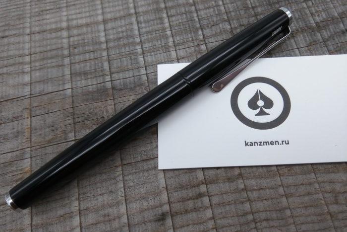 На фотографии закрытая (с надетым колпачком) перьевая ручка LAMY Studio Piano Black на фоне выцветшего дерева, а под ручкой лежит визитка с логотипом и адресом kanzmen.ru