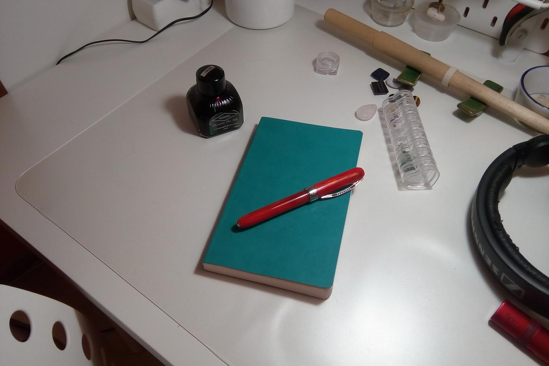 На фото, на рабочем столе, в творческом беспорядке чернила Diamine Oxblood, бизнес-тетрадь Hatber Mint, перьевая ручка Visconti Rembrandt Rosso