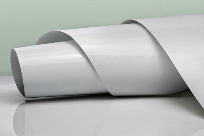 На изображении рулон красиво переливающейся мелованной бумаги